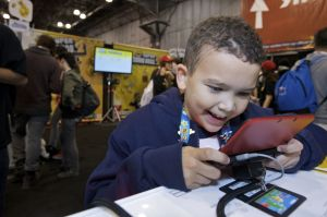 In this photo provided by Nintendo of America, 9 years old Antonio D. of Staten Island, New York competes in a New Super Mario Bros. 2 game-play tournament at the Javits Center in New York on Oct. 12, 2012, for a chance to win a Nintendo 3DS XL portable hand-held system. The Nintendo 3DS XL is a hand-held entertainment device that allows users to play video games, enjoy music videos and trailers, take 3D photos and more. New Super Mario Bros. 2 is one of more than 500 games in the Nintendo 3DS library, which provides an unparalleled list of rich game-play experiences for every age and skill level.