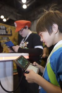 In this photo provided by Nintendo of America, Griffyn B., 8 years old from Connecticut and Ryan M., 11 years old from New Jersey participate in the New Super Mario Bros. 2 game-play tournament at the Javits Center in New York on Oct. 12, 2012. The Nintendo 3DS is a hand-held entertainment device that allows users to play video games, enjoy music videos and trailers, take 3D photos and more. New Super Mario Bros. 2 is one of more than 500 games in the Nintendo 3DS library, which provides an unparalleled list of rich game-play experiences for every age and skill level.