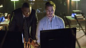 Oliver and Diggle view the files that Arrow had no problem liberating from the police HQ computers.