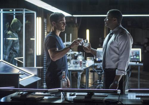 Oliver shares some good hooch with Diggle.